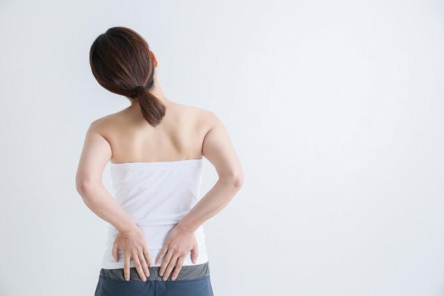 腰を抑える女性 写真